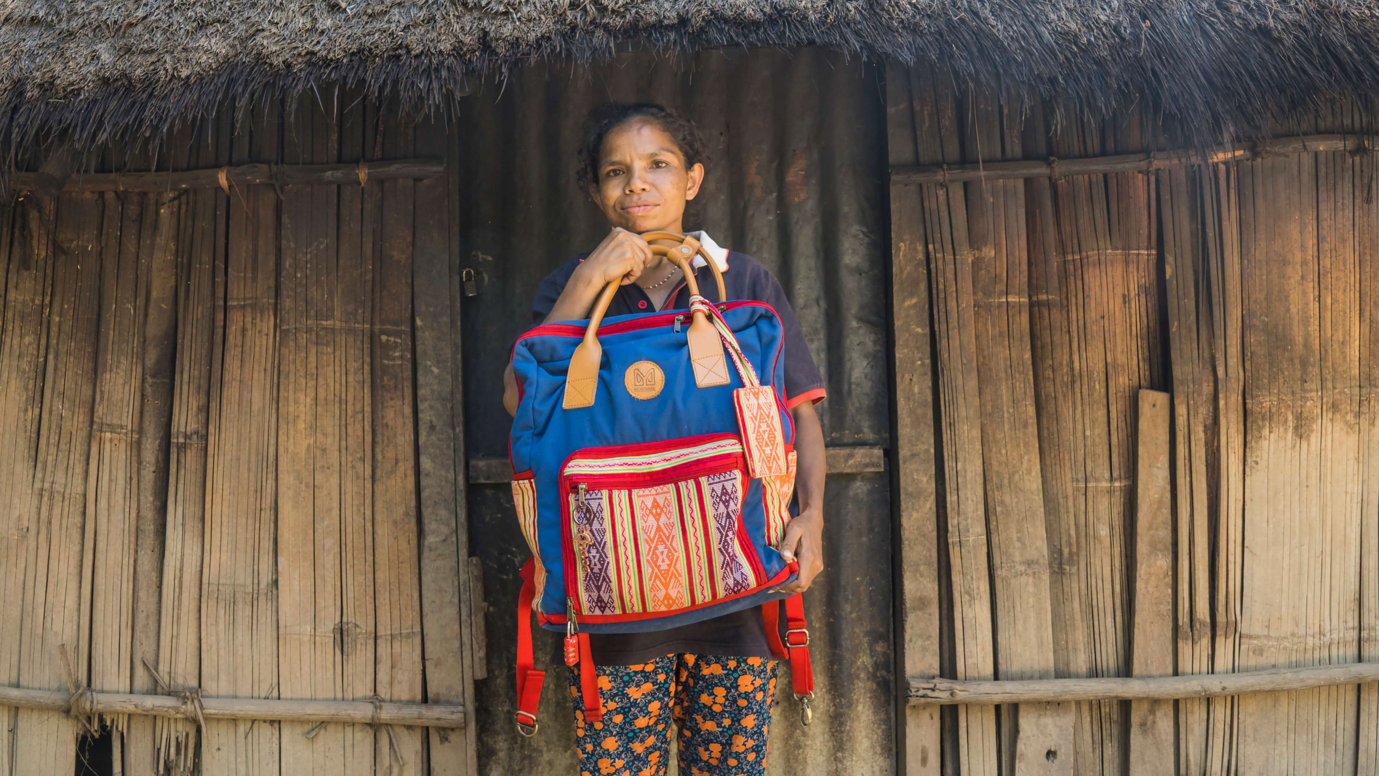 Amelia holds a tenun backpack from a Yogyakarta-based brand that partners with Lakoat.Kujawas to incorporate tenun into their pieces. The tenun is by Amelia.