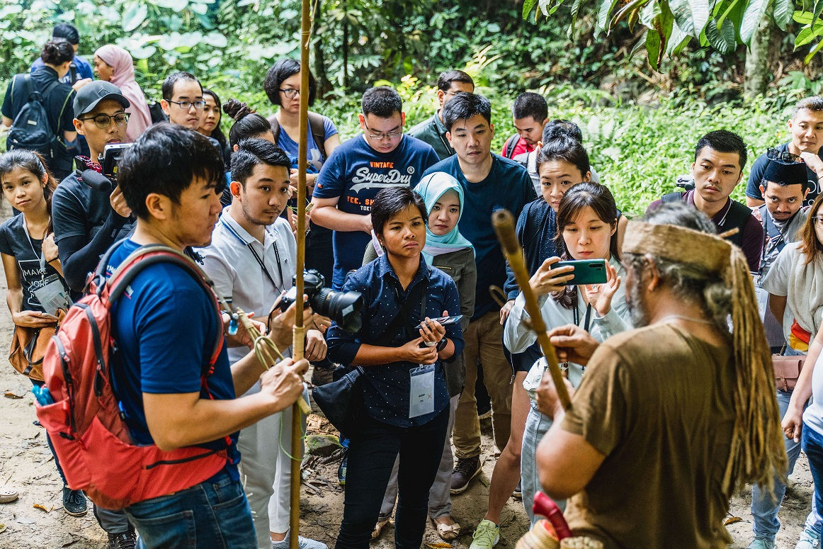 Daniel [far left] co-leads a group on one of Native's (pre-pandemic) tours, where a Temuan guide [foreground] demonstrates blow-pipe hunting. Photo courtesy of Native