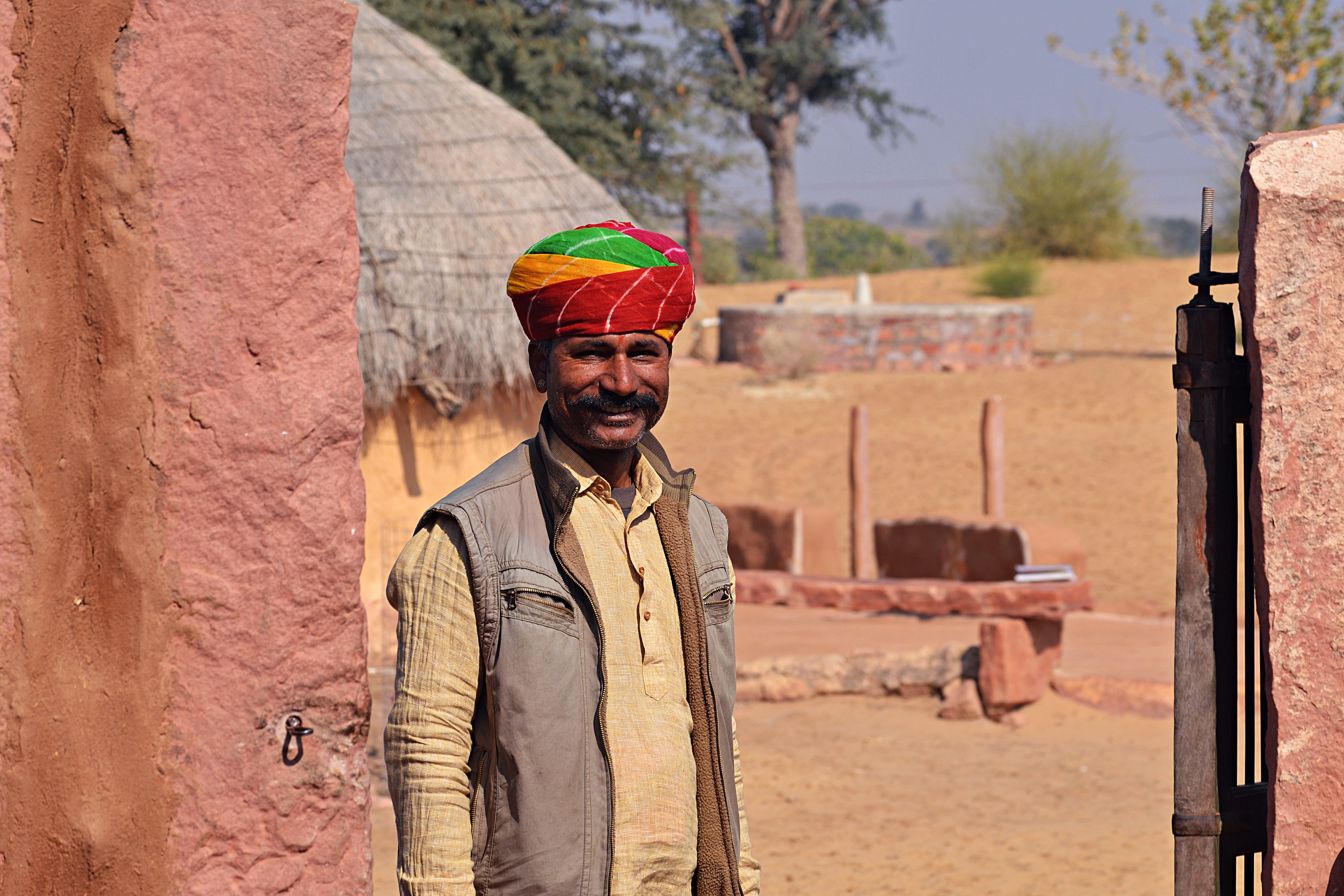 Gemar stands before a jhumpa hut, part of Hacra Dhani, a homestay and tourism social enterprise he founded in the Thar desert.