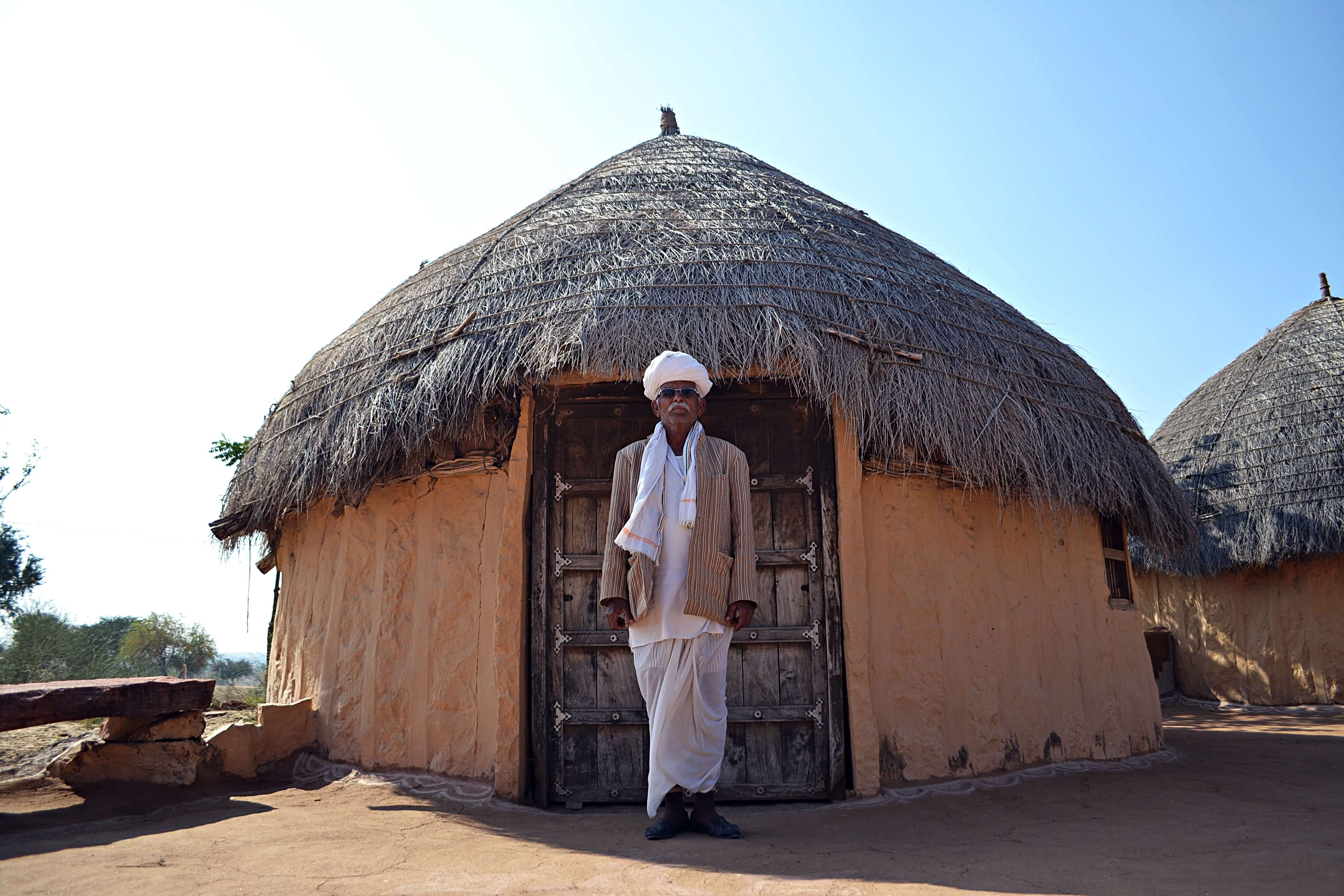Babulal ji, standing in front of  a jhumpa hut. Babulal is one of the guides working for Hacra in an effort to improve the lives of the community via tourism.